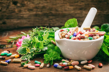 Variety of herbs and pills in a mortar on wooden background. Stockfoto