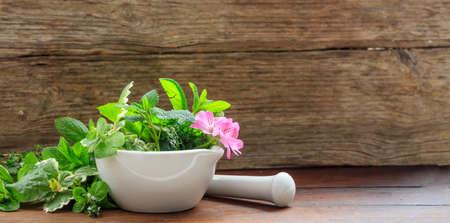 Variety of herbs in a mortar on wooden background Zdjęcie Seryjne