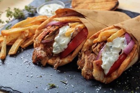Griekse gyros verpakt in pita brood op een zwarte plaat