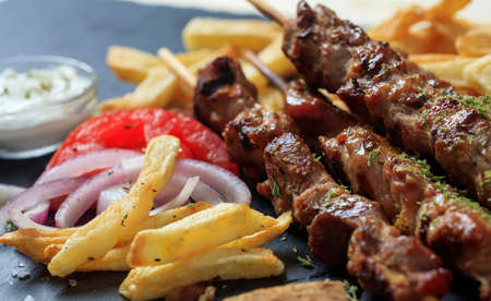 Grilled meat skewers and fried potatoes