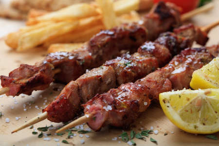 Grilled meat skewers on a baking paper Standard-Bild