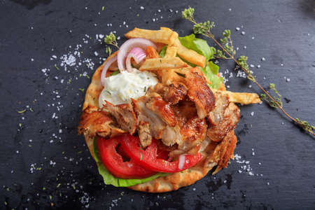 Greek gyros dish on a black plate - top view