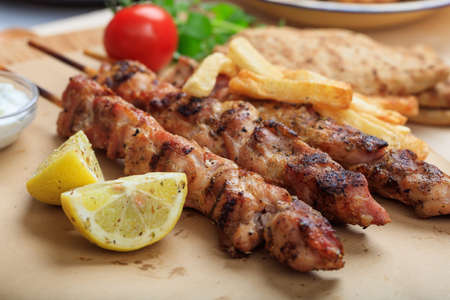 Grilled meat skewers on a baking paper Imagens