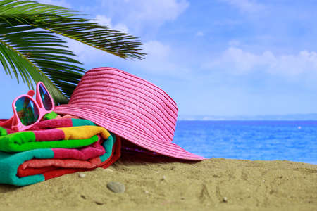 Summer vacations concept - Sunglasses and hat on a sandy beach - copy space