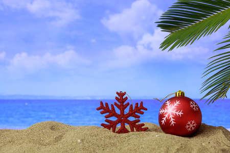 Christmas ball and ornament on a sandy beach - copy space