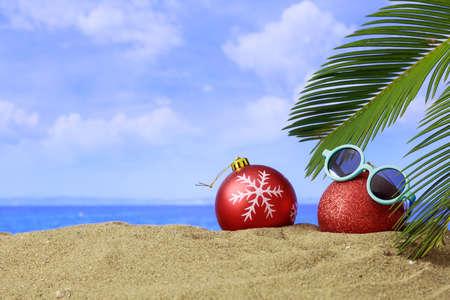 Christmas balls on a sandy beach - copy space