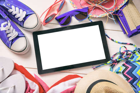 blank screen: Summer vacation accessories and tablet on white wooden background - top view