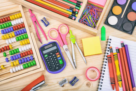 Variety of school supplies on wooden background