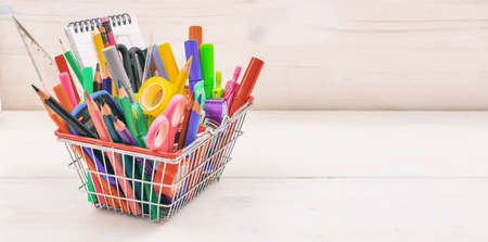 School supplies in a shopping basket on white background Stockfoto