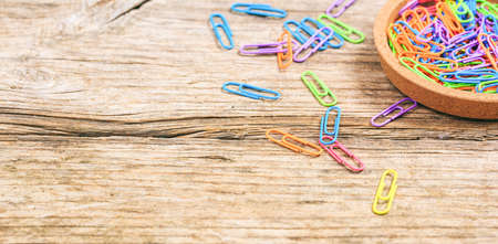 attached: Colorful paper clips on wooden background - copy space