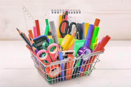 School supplies in a shopping basket on white background Stock Photo