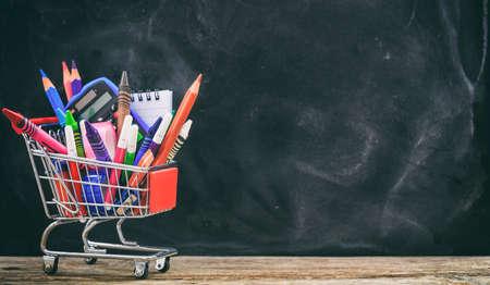 School supplies in a shopping trolley on chalkboard background