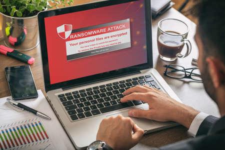 Ransomware alert message on a laptop screen - man at work Foto de archivo