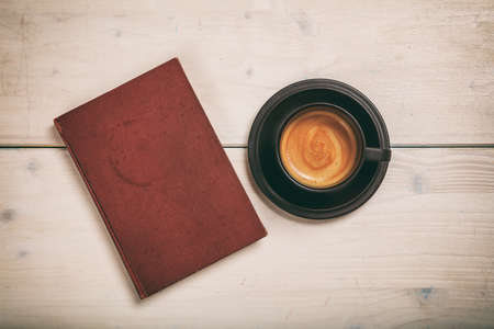 Old book and a cup of coffee on wooden background