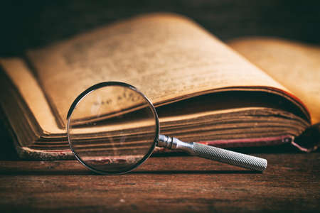 Vintage book and magnifying glass on wooden background Standard-Bild