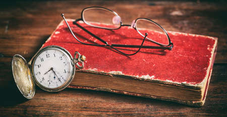 Pocket watch and eye glasses on a vintage book Stock Photo