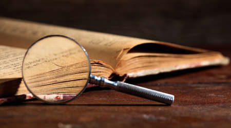 Vintage book and magnifying glass on wooden background Reklamní fotografie