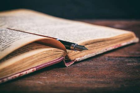 Open vintage book and ink pen on a wooden desk Foto de archivo