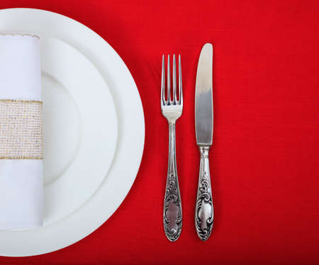 Formal, festive place setting on red tablecloth Stock Photo