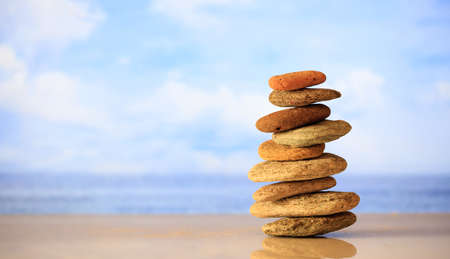 Zen stones stacked on blue sky and sea background