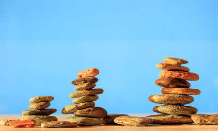 Zen stones stacked on light blue background