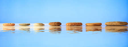 Zen stepping stones on blue background, reflections on the water