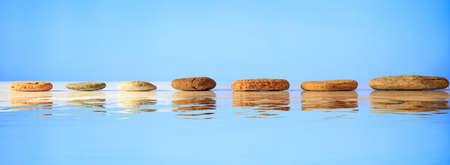 Zen stepping stones op blauwe achtergrond, reflecties op het water