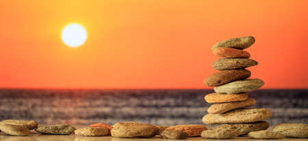 Zen stones stacked on sea background at sunset