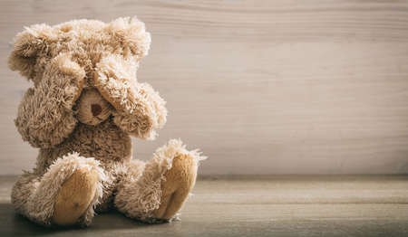 Child abuse concept. Teddy bear covering eyes in an empty room