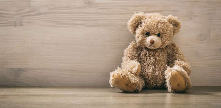 Teddy bear sitting on a wooden background