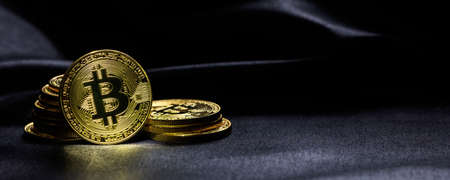 Golden bitcoins stacked on a black texture background