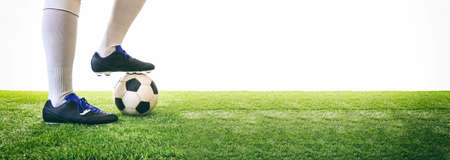 Man controls a soccer ball on the grass. White background and copy space