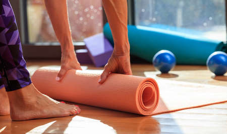 Fitness at home concept. Woman rolling an exercise mat on wooden floor