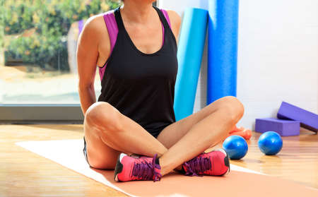 Woman in a fitness class, sitting on an exercise mat, on wooden floor Banco de Imagens