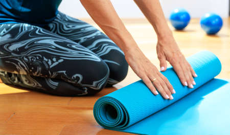 Fitness at home concept. Woman rolling an exercise mat on wooden floor Reklamní fotografie - 87644699