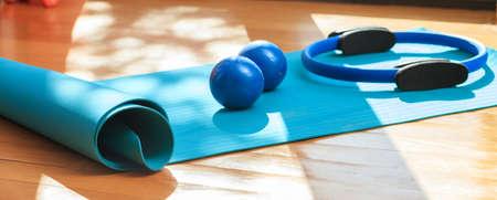 Pilates-Ausrüstung. Übungsmatten und magischer Ring auf Bretterboden Standard-Bild