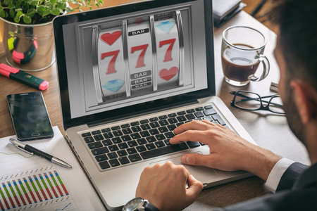 Online gambling concept. Man with a laptop, slot machine on the screen, office background Foto de archivo