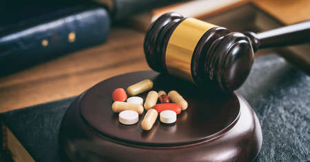 Law gavel and colorful pills on a wooden desk, dark background