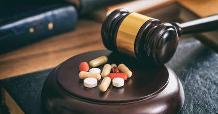 Martelo de lei e pílulas coloridas em uma mesa de madeira, fundo escuro