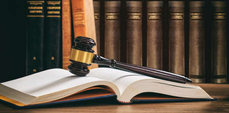 Law gavel on an open book, wooden desk, law books background