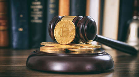 Law or auction gavel and bitcoins on a wooden desk, dark background