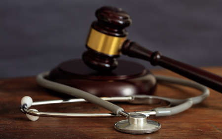 Law gavel and a stethoscope on a wooden desk, dark background