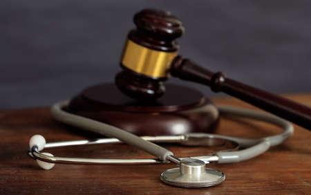 Martillo de la ley y un estetoscopio en un escritorio de madera, fondo oscuro Foto de archivo - 88331559