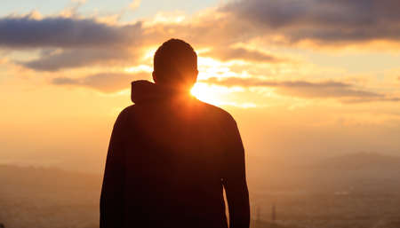 Silhouette of a young man standing alone on the top of a mountain admiring the golden sun and the city. Stok Fotoğraf