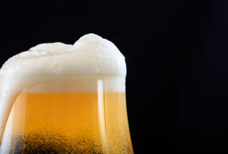 A glass of beer closeup on black background, copy space Imagens