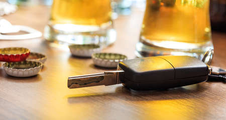 Drinking and driving concept. Car key on a wooden table, pub background