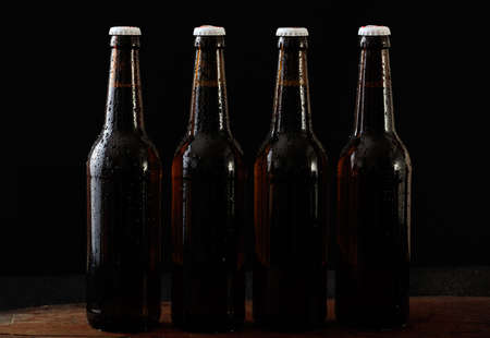 Closeup of four unopened beer bottles isolated on a wooden table, black background