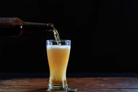 Pouring beer in a glass on a wooden table, dark background. Copy space Stock Photo
