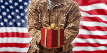 Christmas in the army concept. Christmas ball and gift box on an American soldier uniform Фото со стока - 90013826