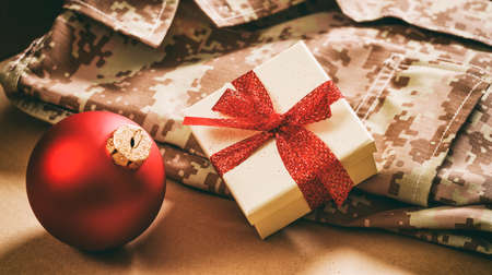 christmas military: Christmas in the army concept. Christmas ball and gift box on an American soldier uniform
